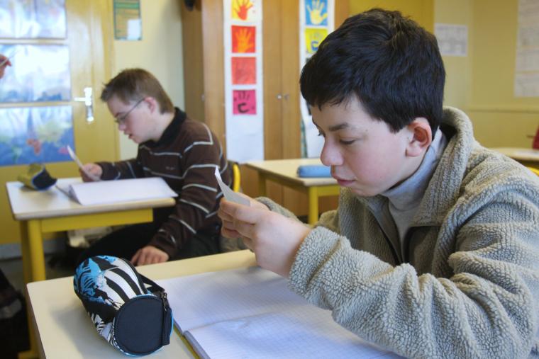 Photo de deux jeunes devant leur bureau d'écolier dans une classe d'intégration scolaire